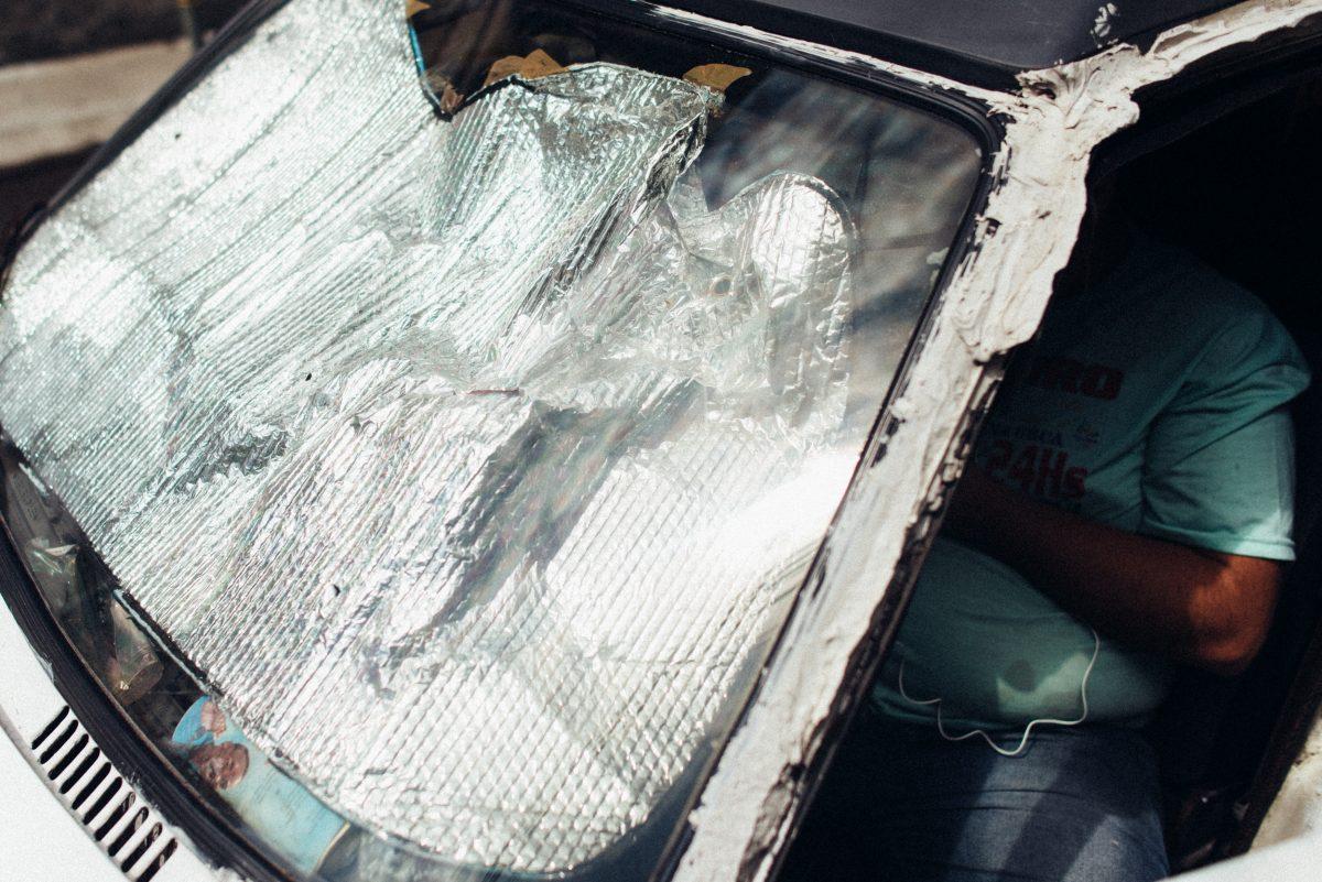 Homem se protege do sol em um carro antigo com protetor solar prateado enquanto usa o celular.